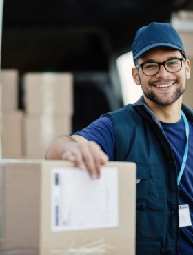 Portrait of happy worker unloading boxes from a delivery van and looking at camera.
